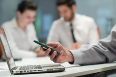 Закройте вверх рук бизнесмена используя умный телефон на встрече Стоковые Изображения