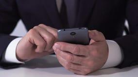 Закройте вверх рук бизнесмена перечисляя финансовые новости на smartphone, передвижной app сток-видео