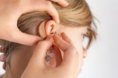 Закройте вверх рук вводя аппарат для тугоухих в ухо стоковое изображение