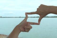 Закройте вверх рук делая рамку для того чтобы показывать Закройте вверх рук женщины Стоковое Фото