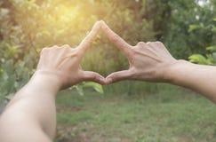Закройте вверх рук делая рамку для того чтобы показывать Конец вверх рук женщины делая рамку показывать с заходом солнца Стоковое фото RF