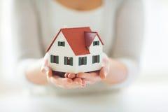 Закройте вверх рук держа модель дома или домашних Стоковая Фотография