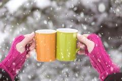 Закройте вверх рук женщины в шерстяных перчатках держа чашки горячего c стоковое фото
