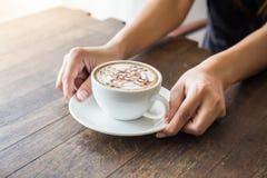 Закройте вверх рук женщины держа белую чашку кофе с красивым искусством картины и деревянным подносом Стоковая Фотография RF