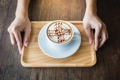 Закройте вверх рук женщины держа белую чашку кофе с красивым искусством картины и деревянным подносом Стоковые Фотографии RF