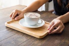 Закройте вверх рук женщины держа белую чашку кофе с красивым искусством картины и деревянным подносом стоковые изображения rf