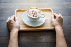 Закройте вверх рук женщины держа белую чашку кофе с красивым искусством картины и деревянным подносом Стоковые Фото