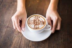 Закройте вверх рук женщины держа белую чашку кофе с красивым искусством картины и деревянный поднос на деревянном столе стоковое фото rf