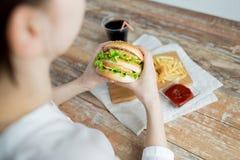 Закройте вверх рук женщины держа гамбургер Стоковые Изображения RF