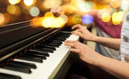 Закройте вверх рук женщины играя рояль над светами Стоковое фото RF
