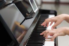 Закройте вверх рук женщины играя рояль на предпосылке Стоковое Фото