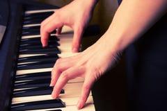 Закройте вверх рук женщины играя рояль Стоковая Фотография