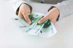 Закройте вверх рук женщины подсчитывая деньги евро Стоковая Фотография RF