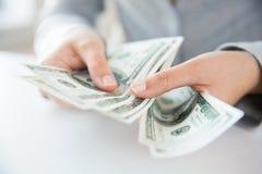 Закройте вверх рук женщины подсчитывая деньги доллара США Стоковое Изображение RF