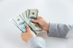 Закройте вверх рук женщины подсчитывая деньги доллара США Стоковые Фото