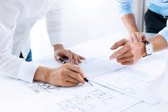 Закройте вверх рук инженера обсуждая проект строительной конструкции на рабочем месте стоковое изображение