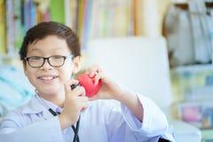 Закройте вверх рук мальчика с сердцем, маленьким милым доктором будущего мальчика стоковое фото rf