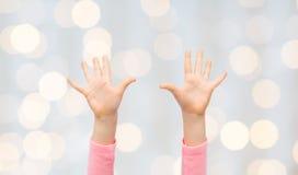Закройте вверх рук маленького ребенка поднятых вверх Стоковые Фотографии RF