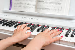 Закройте вверх рук молодой женщины играя рояль Стоковая Фотография