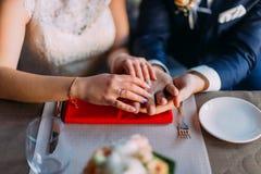 Закройте вверх рук нов-пожененных пары нося обручальные кольца на, который служат таблице с kitchenware Стоковая Фотография RF