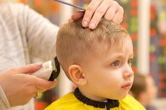 Закройте вверх рук парикмахера Женщина стоящ и делающ стрижка для малого мальчика Она держит клипер волос стоковое фото rf