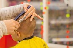 Закройте вверх рук парикмахера Женщина стоящ и делающ стрижка для небольшого мальчика Она держит гребень и ножницы стоковая фотография