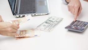 Закройте вверх рук подсчитывая деньги с калькулятором Стоковое фото RF