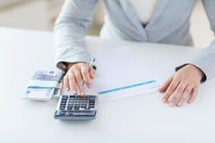Закройте вверх рук подсчитывая деньги с калькулятором Стоковое Фото