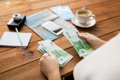Закройте вверх рук путешественника подсчитывая деньги евро Стоковые Изображения