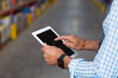 Закройте вверх рук работника используя таблетку стоковое изображение rf