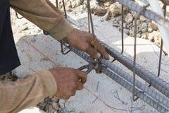 Закройте вверх рук рабочий-строителя работая с пинцетами Стоковые Фото