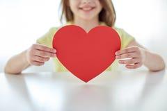 Закройте вверх рук ребенка держа красное сердце Стоковые Изображения