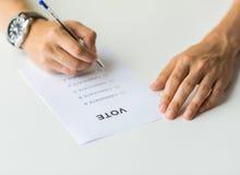 Закройте вверх рук с голосованием или баллотируйте на избрании стоковое изображение