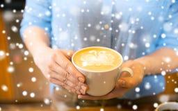 Закройте вверх рук с искусством latte в кофейной чашке стоковые изображения