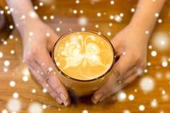 Закройте вверх рук с искусством latte в кофейной чашке стоковое изображение