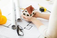 Закройте вверх рук с моделью дома над светокопией Стоковое Изображение RF