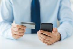 Закройте вверх рук с умными телефоном и кредитной карточкой стоковые изображения rf