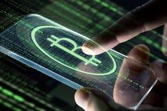 Закройте вверх рук с smartphone и bitcoin стоковое изображение