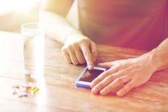 Закройте вверх рук с smartphone, пилюльками и водой Стоковые Изображения RF