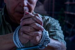 Закройте вверх рук человека обернутых с веревочкой вокруг запястьев руки в плене, злоупотребленной жертвы, раба работы, уважения  стоковые изображения rf