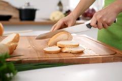 Закройте вверх рук ` s женщины варя в кухне Домохозяйка отрезая белый хлеб Вегетарианец и здорово варить Стоковые Фото