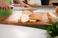 Закройте вверх рук ` s женщины варя в кухне Домохозяйка отрезая белый хлеб Стоковые Изображения RF