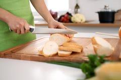 Закройте вверх рук ` s женщины варя в кухне Домохозяйка отрезая белый хлеб Вегетарианец и здорово варить Стоковая Фотография RF