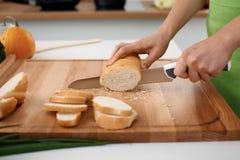 Закройте вверх рук ` s женщины варя в кухне Домохозяйка отрезая белый хлеб Вегетарианец и здорово варить Стоковое Изображение RF
