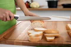 Закройте вверх рук ` s женщины варя в кухне Домохозяйка отрезая белый хлеб Вегетарианец и здорово варить Стоковое фото RF