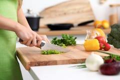 Закройте вверх рук ` s женщины варя в кухне Домохозяйка отрезая свежий салат Вегетарианец и здорово варить Стоковое Фото