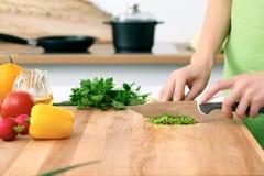 Закройте вверх рук ` s женщины варя в кухне Домохозяйка отрезая свежий салат Стоковое Изображение