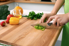 Закройте вверх рук ` s женщины варя в кухне Домохозяйка отрезая свежий салат Стоковая Фотография RF