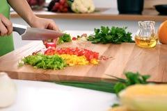Закройте вверх рук ` s женщины варя в кухне Домохозяйка отрезая свежий салат Вегетарианец и здорово варить Стоковая Фотография