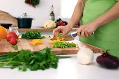 Закройте вверх рук ` s женщины варя в кухне Домохозяйка отрезая свежий салат Вегетарианец и здорово варить Стоковые Фотографии RF